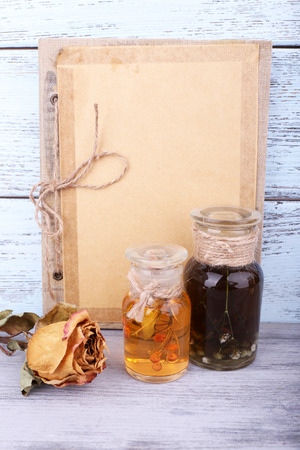 tincture: Bottles of herbal tincture, book and dried rose on wooden background