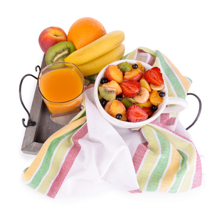 Fresh fruits salad in bowl with juice on wooden tray isolated on white photo