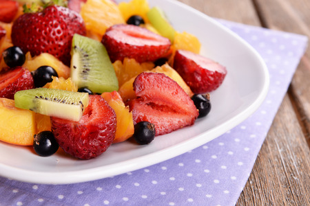 Fresh fruits salad on plate with on table close up photo
