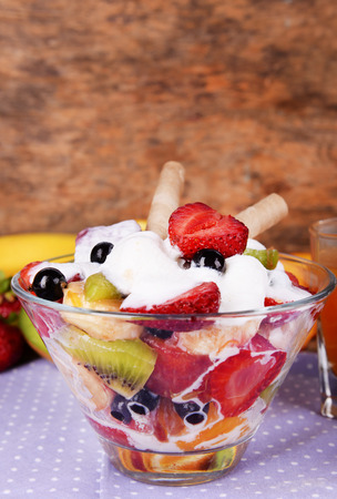 Fresh fruits salad with ice cream in bowl and fruits on table close up photo