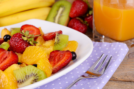 Fresh fruits salad on plate with juice on table close up photo