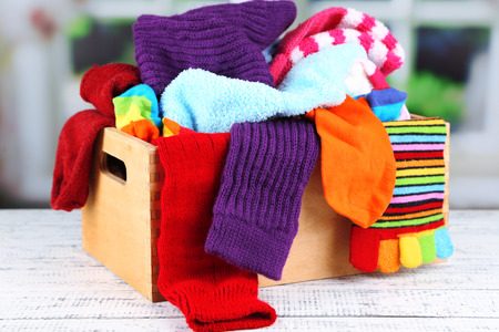white sleeve: Multicoloured socks in a box on a wooden table in front of the window