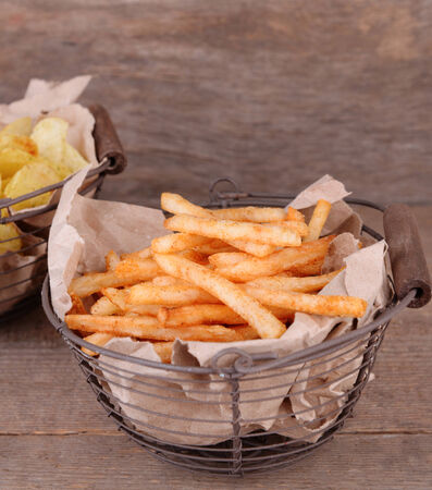 Tasty french fries in metal basket and potato chips on wooden table photo