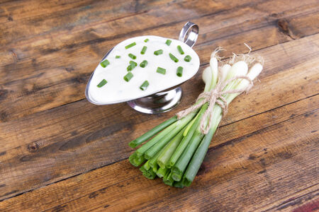 tuft: Metal bowl of cream with a tuft of onion near it on wooden background