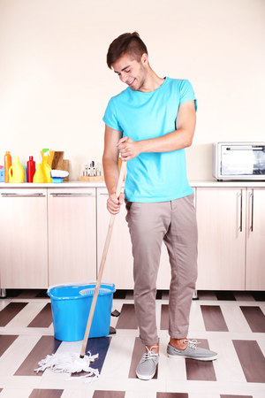 Young man cleaning floor in room Stock Photo