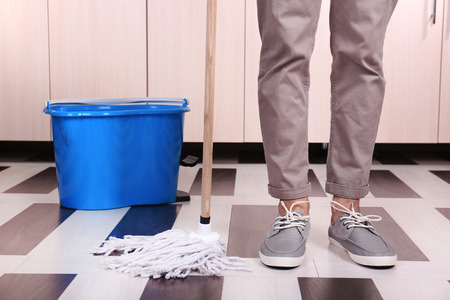 Junger Mann Reinigung Boden im Zimmer Standard-Bild
