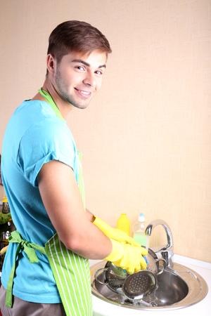 Man washing dish in kitchen