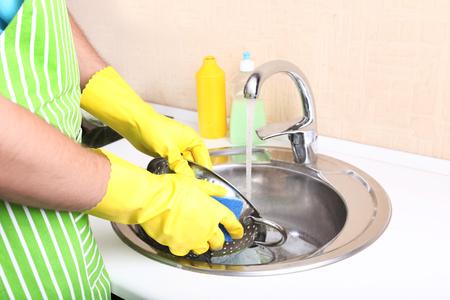 Man washing dish in kitchen photo