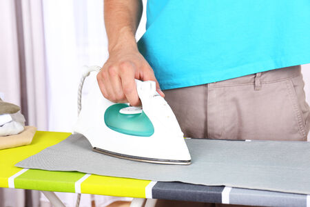 iron curtain: Young man ironing clothes in room Stock Photo