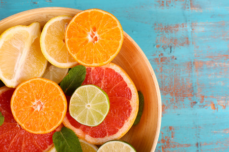 juicy: Different sliced juicy citrus fruits in bowl on blue wooden table