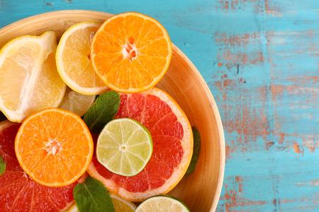 witaminy: Różne plasterki soczyste owoce cytrusowe w misce na niebieskim drewnianym stole