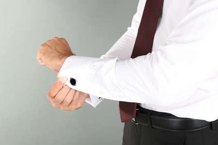 Man doing collar button up on grey background photo