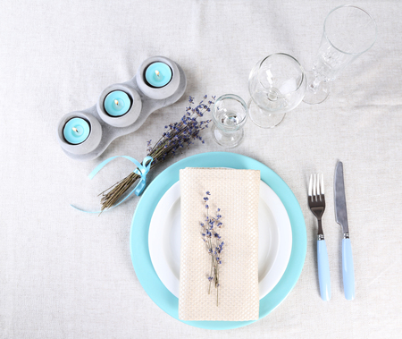 Dining table setting with lavender flowers on table, on light background photo