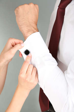 Woman helping man to do collar button up on grey background photo