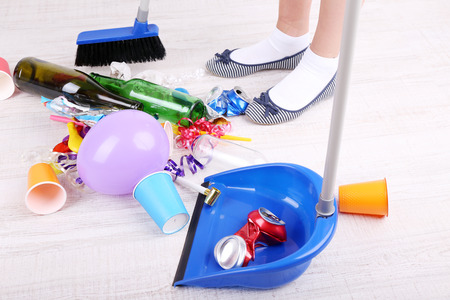 Woman cleaning grey wooden floor from mess Stock Photo