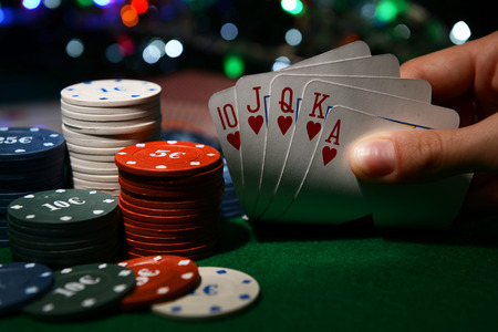 royal flush: Chips and cards for poker in hand on green table