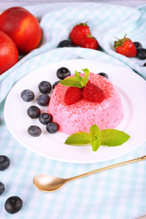 Round shaped cake with berries on plate on table cloth photo