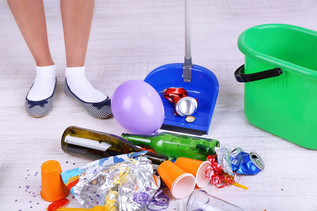mess: Woman cleaning grey wooden floor from mess Stock Photo