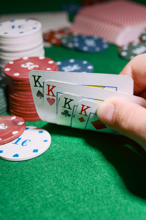 lear: Chips and cards for poker in hand on green table