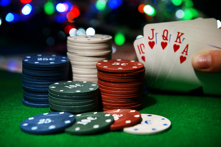 Chips and cards for poker in hand on green table photo
