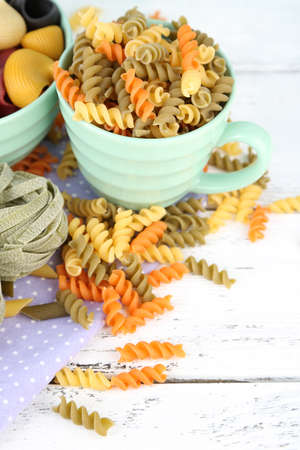 Colorful pasta in color bowls and mugs on wooden background photo