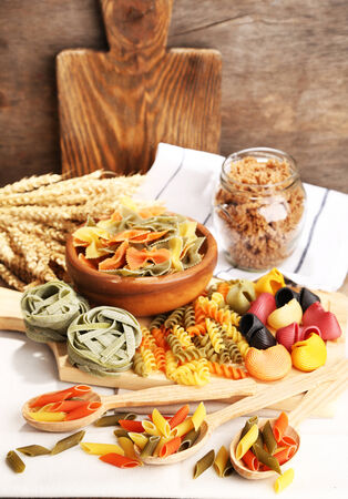 Variety of colorful pasta on wooden background photo