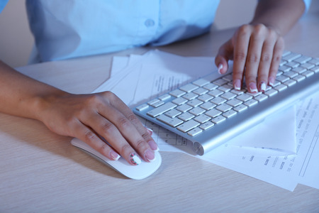 Female hand holding computer mouse, close-up photo