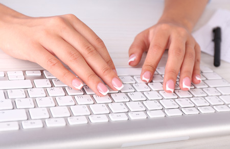Female hands typing on keyboard, close-up, on dark background photo