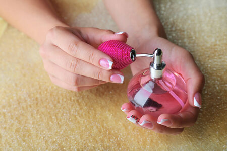 Female hand  holding bottle with perfumes on bright background photo