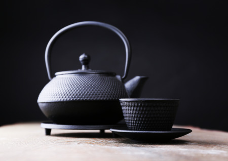 stand teapot: Chinese traditional teapot on wooden table, on dark background
