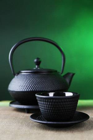 antique dishes: Chinese traditional teapot on wooden table, on dark color background