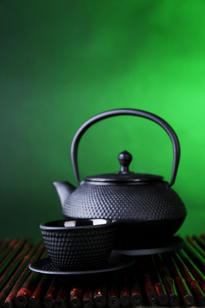 stand teapot: Chinese traditional teapot on bamboo mat, on dark color background Stock Photo