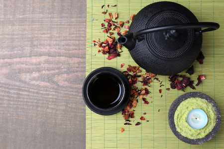 stand teapot: Black teapot, bowl and tea on wooden background Stock Photo