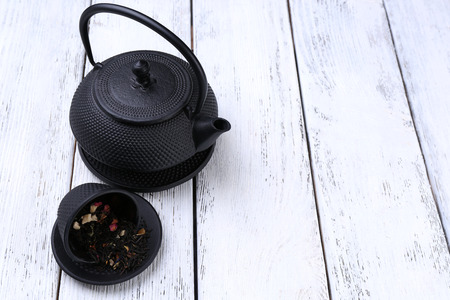 stand teapot: Black teapot, bowl and tea on color wooden background Stock Photo