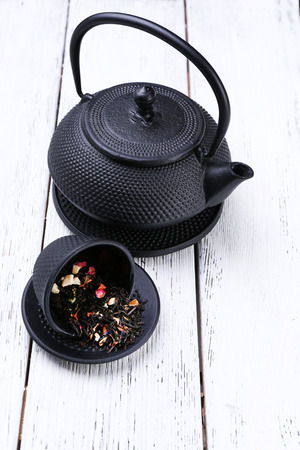Black teapot, bowl and tea on color wooden background photo