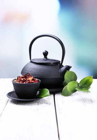 Black teapot, bowl and tea on color wooden table, on bright background photo