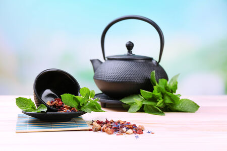 stand teapot: Chinese traditional teapot with fresh mint leaves and dried hibiscus petals on wooden table, on bright background Stock Photo