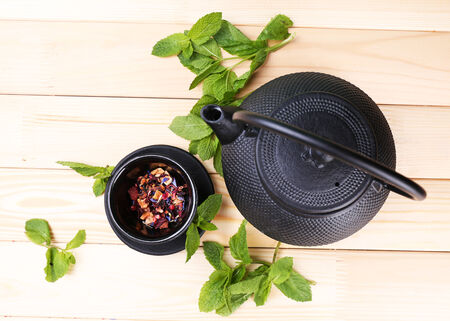 stand teapot: Chinese traditional teapot with fresh mint leaves and dried hibiscus petals on wooden background Stock Photo