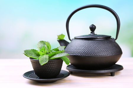 stand teapot: Chinese traditional teapot with fresh mint leaves on wooden table, on bright background Stock Photo