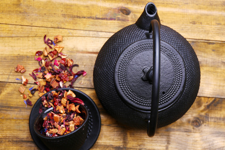 stand teapot: Black teapot, bowl and hibiscus tea on color wooden background