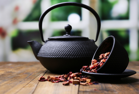 Black teapot, bowl and hibiscus tea on color wooden table, on bright background Stockfoto