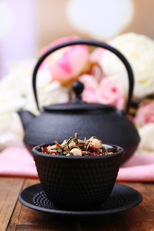 stand teapot: Black teapot, bowl and hibiscus tea on color wooden table, on bright background Stock Photo
