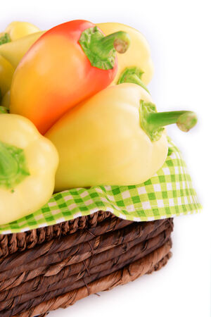 Yellow peppers in basket isolated on white photo