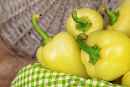 Yellow peppers in basket on wicker background photo