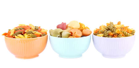 Assortment of colorful pasta in color bowls isolated on white photo