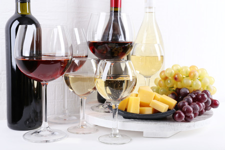 Bottles and glasses of wine, cheese and ripe grapes on table in room photo