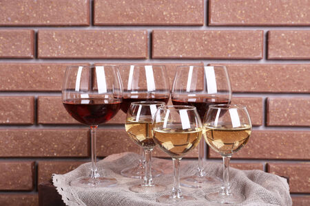 Glasses of wine on box on brick wall background photo