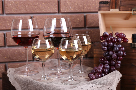 Bottle and glasses of wine and ripe grapes on table on brick wall background photo