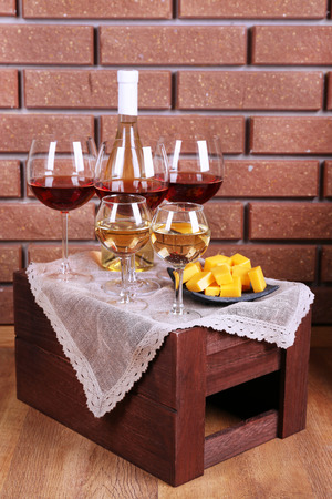 Bottle and glasses of wine and cheese on table on brick wall background photo