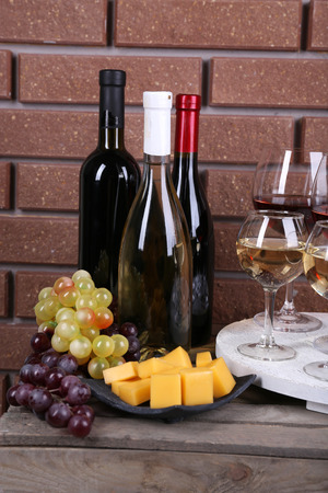 Bottles and glasses of wine, cheese and ripe grapes on box on brick wall background photo